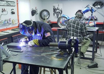 A couple of guys learning the TIG welding skill needed for welding the bungs and brackets needed to attach fenders, gas tanks and oil tanks. After 6 hours they are usually able to weld vertical and overhead.